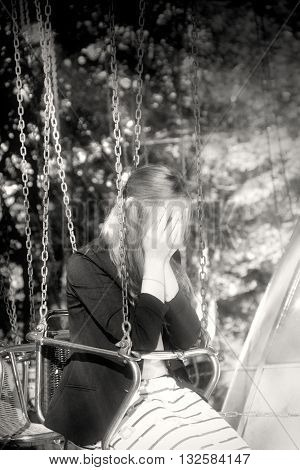 Attractive fashionable blonde outdoors. Hands on face. Sorrow and grief emotions. Carousel seat with chain