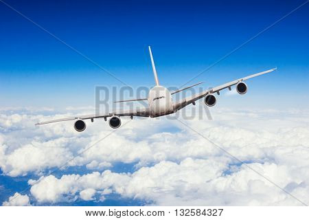 Commercial jet plane flying above clouds in day light