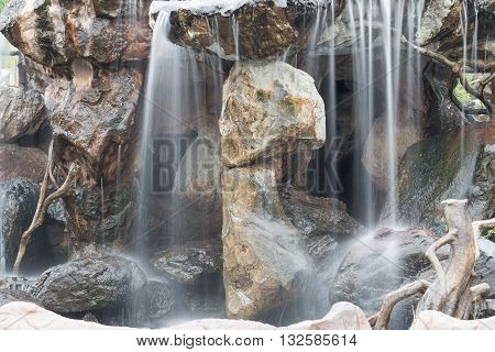 Waterfall flowing over rocks in the garden. Beautiful of waterfalls with soft flowing water and large rocks.( Blur blurred Waterfall)