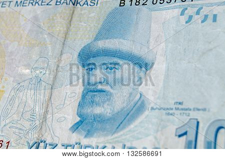 A used 100 Turkish Lira banknote showing the composer Buhurizade Mustafa Itri. Banknote photographed at an angle.