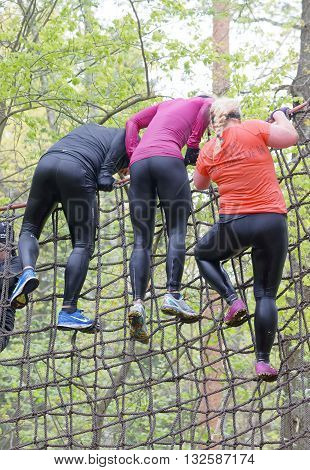 STOCKHOLM SWEDEN - MAY 14 2016: Group of woman climbing up a net in the obstacle race Tough Viking Event in Sweden May 14 2016