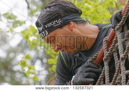 STOCKHOLM SWEDEN - MAY 14 2016: Closeup of a man climbing up a net in the obstacle race Tough Viking Event in Sweden May 14 2016