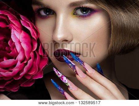 Beautiful girl with colorful make-up, flowers, retro hairstyle and long nails. Manicure design. The beauty of the face. Photos shot in studio