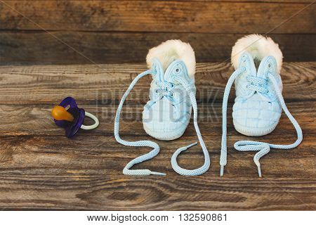 2017 new year written laces of children's shoes and pacifier on old wooden background. Toned image
