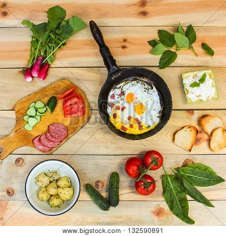 Different food: scrambled eggs in frying pan, boiled potatoes, curd, croutons, radishes, cucumbers, tomatoes, smoked sausage, croutons, mint, sorrel on wooden table. Toned image