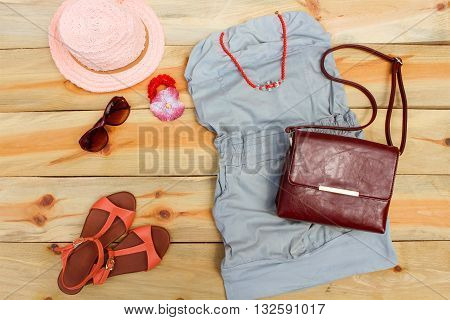 Women's summer clothing and accessories on wooden background. Toned image.
