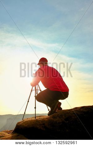 Photographer In Red Jacket And Red Baseball Cap  Stay With Camera On  Tripod On Cliff And Thinking.