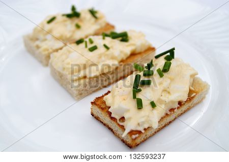 Toast and egg spread on white plate with chive