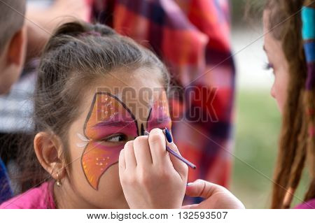 TIMISOARA ROMANIA - JUNE 01 2016: Workshop with face painting for children in a park in Timisoara Romania. International children Day.