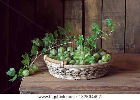 Green gooseberries in a basket on the table. Still life with gooseberries on the background boards.