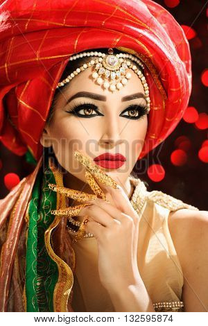 Portrait of a beautiful female model wearing a turban and ethnic jewellery on the head looking exotic