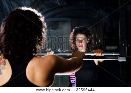 A weight trainer focuses in the mirror before lifting the barbell. Dramatic lighting intensifies the mood of the scene.