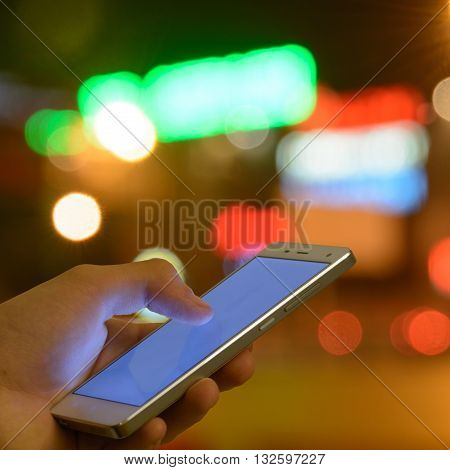 Man touch screen mobile phone night lights bokeh background