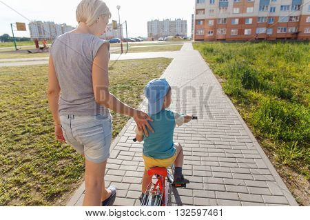 Mom helps son to ride a Bicycle for the first time
