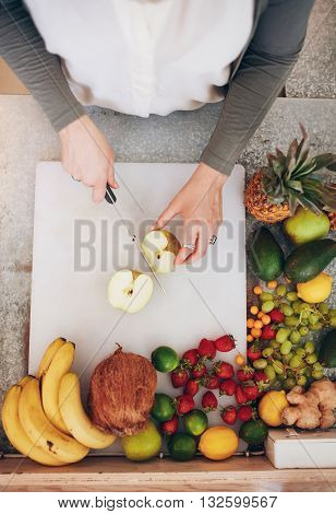 Female Employee Working At Juice Bar Cutting An Apple