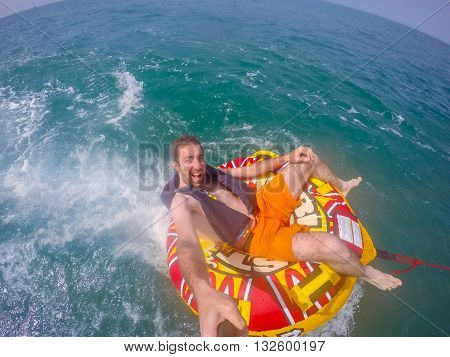 Man sitting in inflatable ring towed by a boat in the water and photographing himself with Go Pro camera.