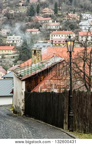 Street with ancient houses in the old town Banska Stiavnica Slovak republic Unesco. Cultural heritage. Architectural theme. Street light. Vertical composition. Red roofs.