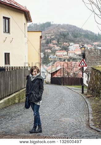 Young tourist woman posing in historical street in Banska Stiavnica Slovak republic. Travelling theme. Travel destination. Positive woman. Traffic sign.