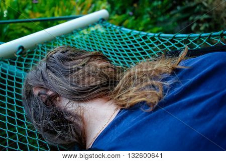 Woman laying down on a hammock and her face covered by her hairs.