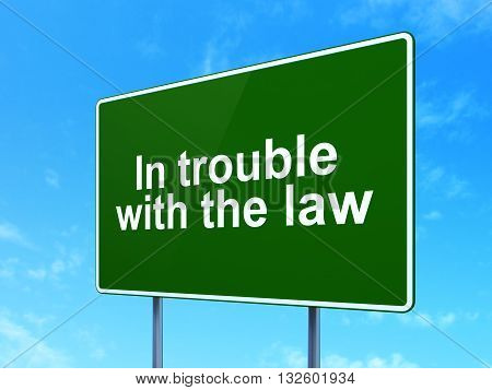 Law concept: In trouble With The law on green road highway sign, clear blue sky background, 3D rendering