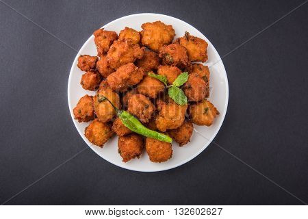 Delicious Tasty and Yummy Indian snacks made using Split Green gram known as Moong Dal vada or moong dal pakoda or moong vada or moong vade or Pakora (Fritter) with fried green chilli, red and green hot sauce.