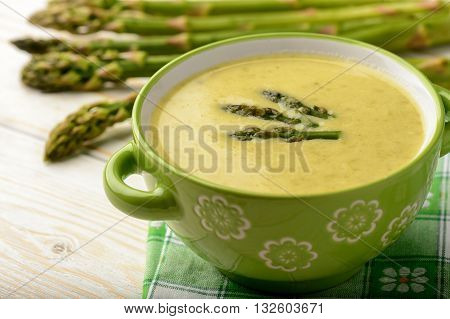 Green asparagus cream soup on wooden background.
