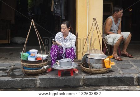 Hoi An, Vietnam - Jun 20, 2015: Vietnamese food vendor selling traditional cakes and noodles on a street side in Hoi An ancient town. Hoi An is recognized as a World Heritage Site by UNESCO.