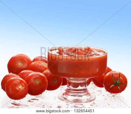 FRESH , RAW TOMATO SAUCE IN A GLASS , SURROUNDED WITH FRESH CHERRY TOMATOES , ON GRADIENT BLUE - WHITE BACKGROUND