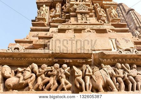 Stone people horses and elephants on reliefs of Hindu temple in Khajuraho, India. UNESCO Heritage site built between 950 and 1150 in India belong to Hinduism and Jainism.