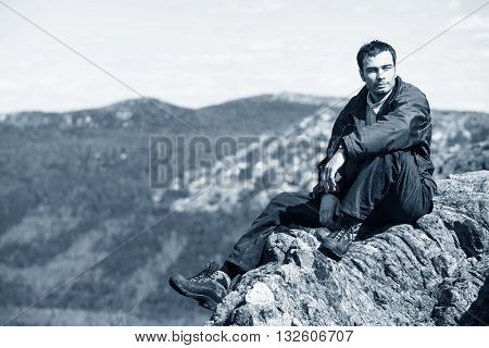 Tourist man sitting on the top of rock