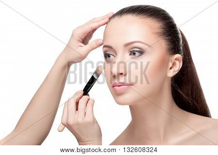the makeup artist applied with a Foundation brush on the face. perfect skin women. makeup for brunettes