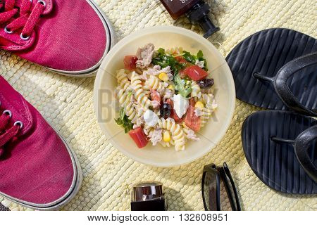 shoes and flip-flop with sunglass suntan cream and pasta salad for a concept of summer time