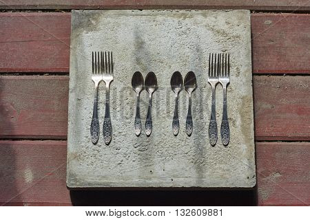 four forks and little spoons on concrete and wood floor