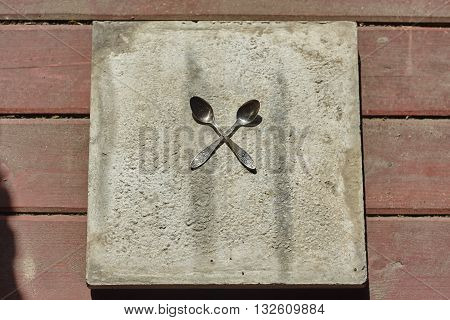 two crossed little spoons on concrete and wood floor