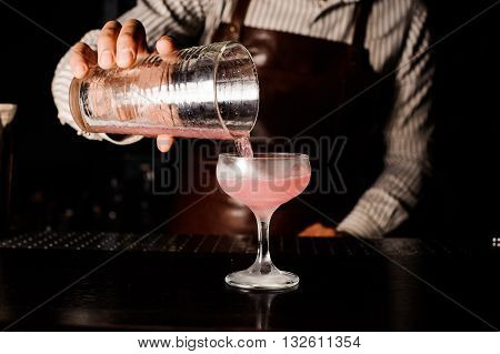 barman preparing and pouring cosmopolitan alcoholic cocktail drink at bar. Alcoholic drink with vodka, triple sec, cranberry juice and lemon juice