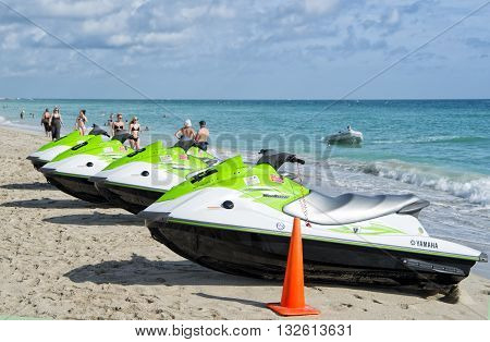 Miami Florida USA-January 10 2016: green and white jet ski yamaha standing in row on sandy beach sunny day at South Beach Florida USA