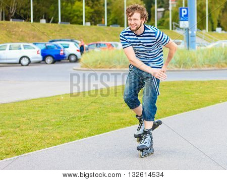 Holidays active lifestyle freedom concept. Young fit man on roller skates riding outdoors on street guy rollerblading on sunny day