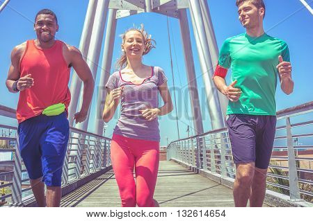 jogging together - group of 3 young people running and smiling on a sunny day on a bridge