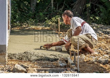 Labuan,Malaysia-April 7,2016:Undentified construction local worker doing concrete cement floor topping with float at construction Layang-Layang,Labuan,Malaysia.