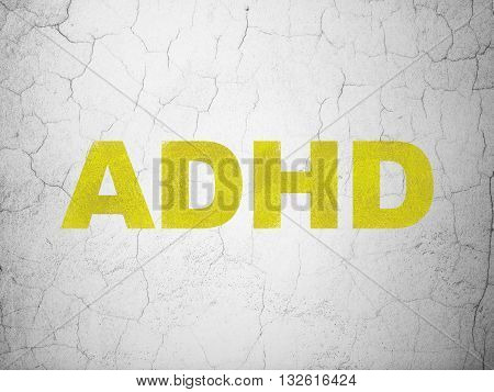 Health concept: Yellow ADHD on textured concrete wall background