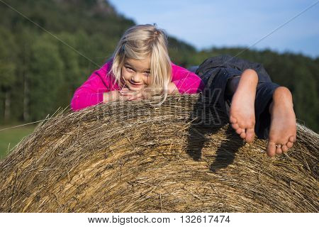 Children blond girl and boy (siblings) resting on hay bale, summer, holiday, relaxing, playing