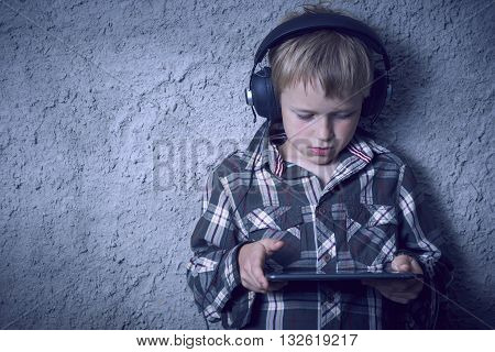 Child blond Boy listening to music or watching movie with headphones and using digital tablet. Concrete wall background