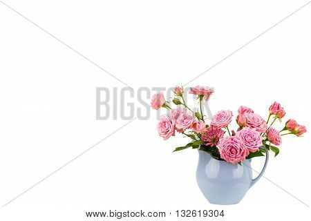Pink flowers in blue jug. Roses in jug. Isolation. Postcard background. Wedding card background. Wedding invitation. Pink roses. Pink roses in a light blue vase on white background with copy space.