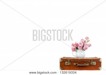 Pink flowers in jug on old brown vintage suitcase. Roses in jug. Pink roses. Shabby chic. Rustic concept.