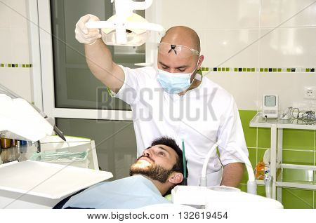 Dantist at work. Dentist examining a patients teeth. Patient in a dental chair
