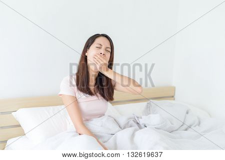 Woman feeling tired on bed