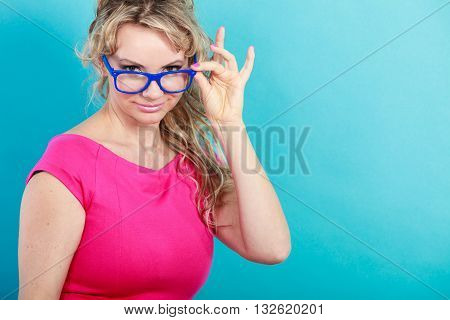 Portrait of mid age attractive woman. Elegant female curly blonde hair posing in vivid color clothing and glasses. Bright fashion. Optics eyewear. Studio shot on blue background.