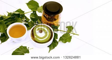 Cake tea matcha green tea for print or promote Prob have Mulberry leaf in my plant and green tea in pot ceramic cup background white color have Space areas keep right for your word or logo
