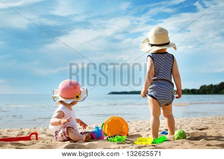 Babygirl and babyboy on the beach in straw hats