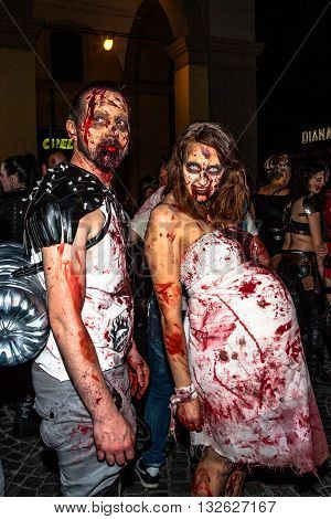 Bologna, Italy - May 21, 2016: Bologna zombie apocalypse walk: a pregnant zombies bloody woman walking at night through the streets of the city.